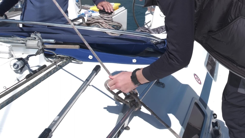 Male hands of the yachtsman untie the rope in order to raise the sail on the yacht Royalty-Free Stock Footage #1071561616