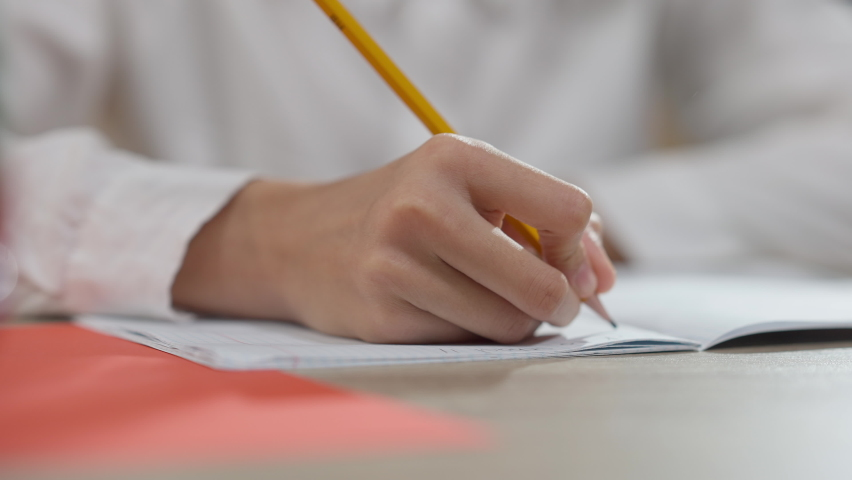 Close-up of African American hand writing in workbook with pencil. Unrecognizable junior high student handwriting at desk in classroom. Education and diligence concept Royalty-Free Stock Footage #1071604453