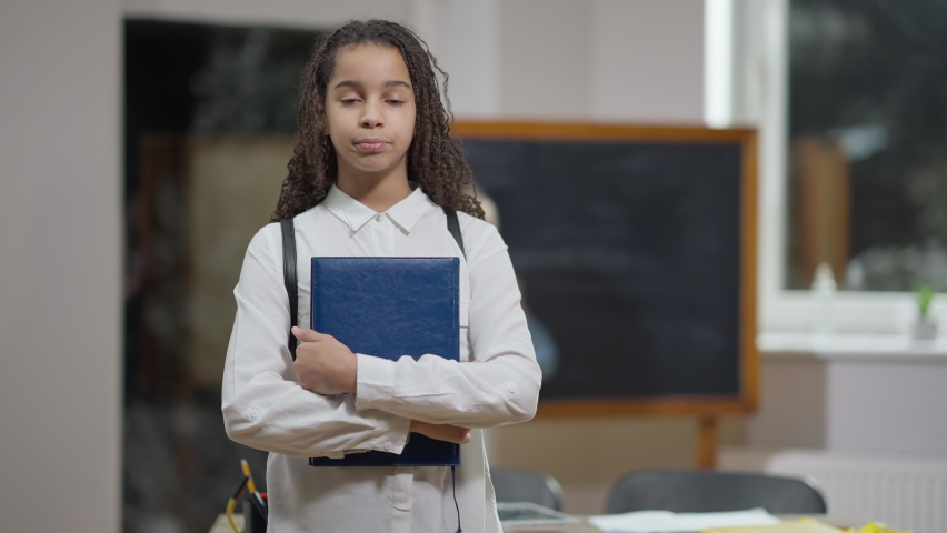 Middle shot portrait of positive cute African American schoolgirl with workbook posing in classroom with blurred Caucasian classmate at background. Happy confident girl standing in school indoors Royalty-Free Stock Footage #1071604459