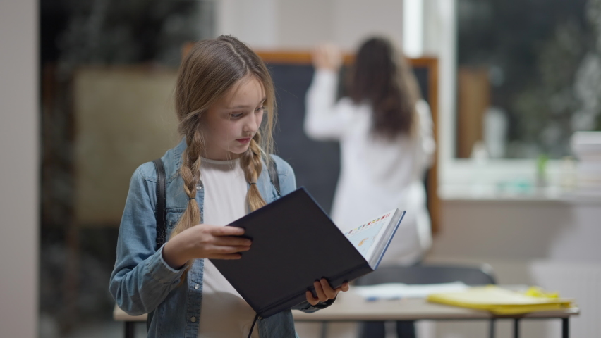 Charming smart Caucasian schoolgirl closing workbook and smiling looking at camera. Blurred African American classmate at background in classroom. Portrait of happy girl posing in school indoors Royalty-Free Stock Footage #1071604462