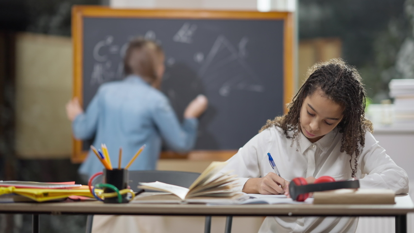 Stressed African American schoolgirl sighing having problems as Caucasian smart classmate helping friend with math. Friendly girls studying in secondary school. Intelligence and friendship Royalty-Free Stock Footage #1071604483