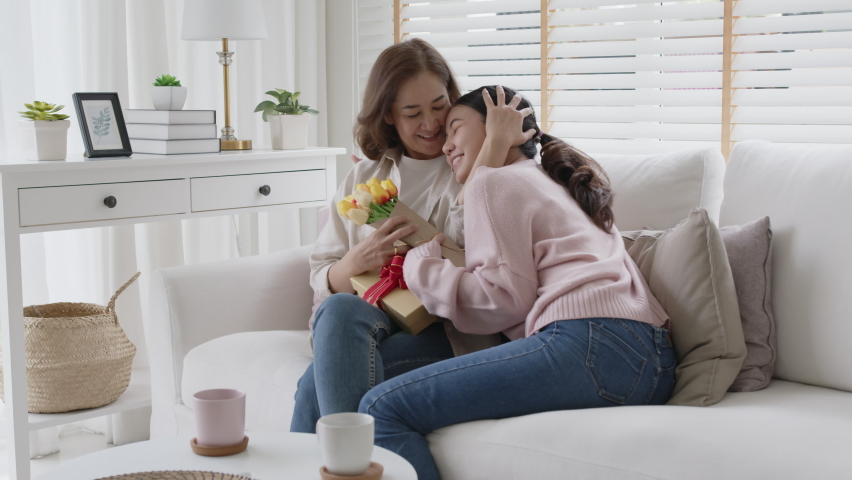 Attractive beautiful asian middle age mum sit with grown up daughter give gift box and flower in family moment celebrate mother day. Overjoy bonding cheerful kid embrace relationship with retired mom. Royalty-Free Stock Footage #1071686491