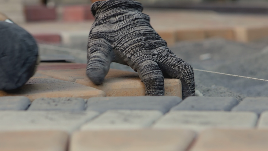 4K Details with hands of a mason working with cobblestone . Construction worker laying paving slabs on the street. Engineer on protective gloves makes the sidewalk , hitting stone with hammer   Royalty-Free Stock Footage #1071687541