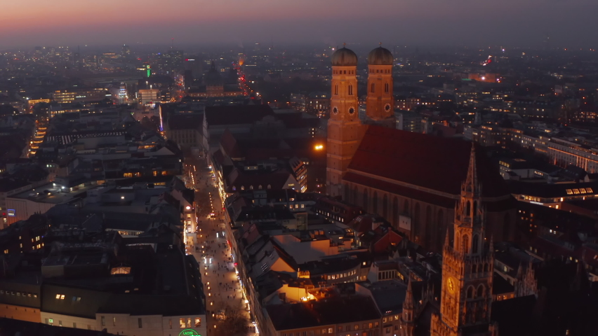 The Famous Frauenkirche Church Cathedral in Munich at Night, Aerial Dolly forward approaching two towers of beautiful old building, Scenic City Lights glowing