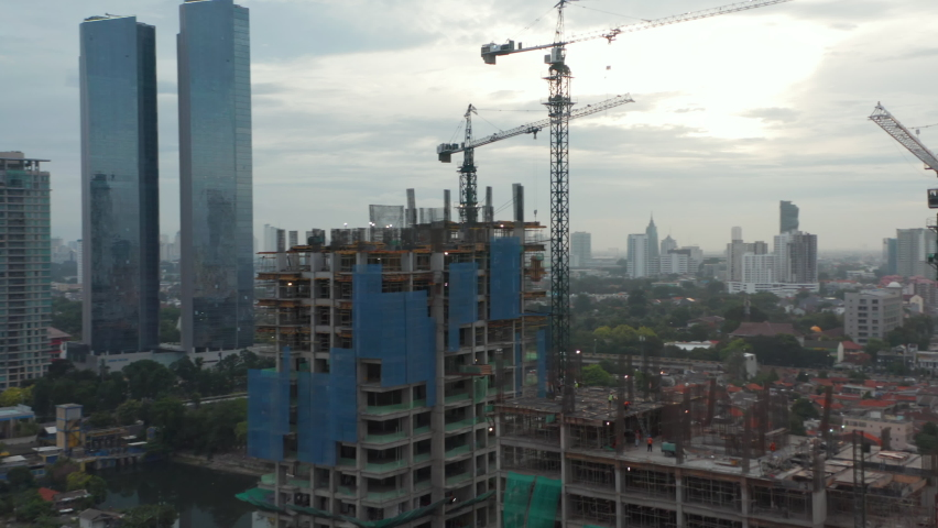 Close up aerial view of crane lowering an object on the roof of the skyscraper under construction in Jakarta, Indonesia Royalty-Free Stock Footage #1071746842
