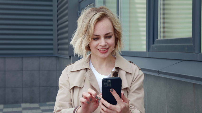Upset business woman looking with horror at the smartphone screen and covers her mouth with her hand in fear. Surprised caucasian woman reading terrible news on mobile phone while stands outdoors