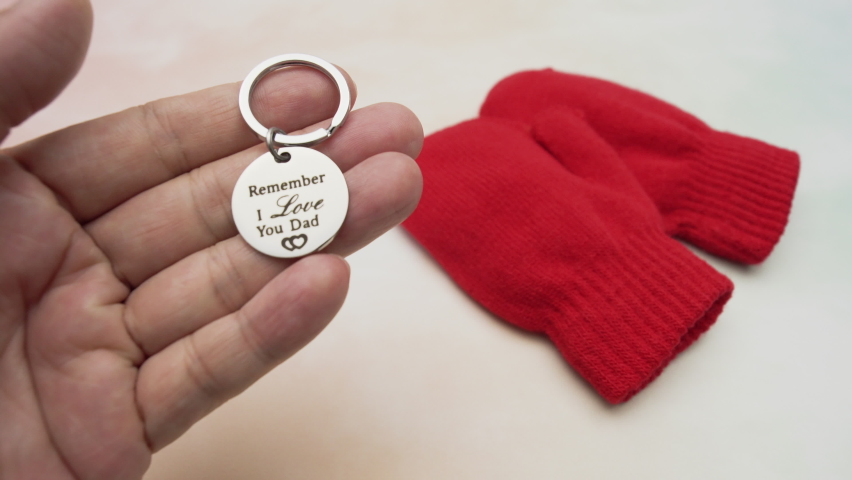 Happy family scene of dad missing child by picking up love key chain gift near child gloves on stone background, father receive key chain from child on father's day