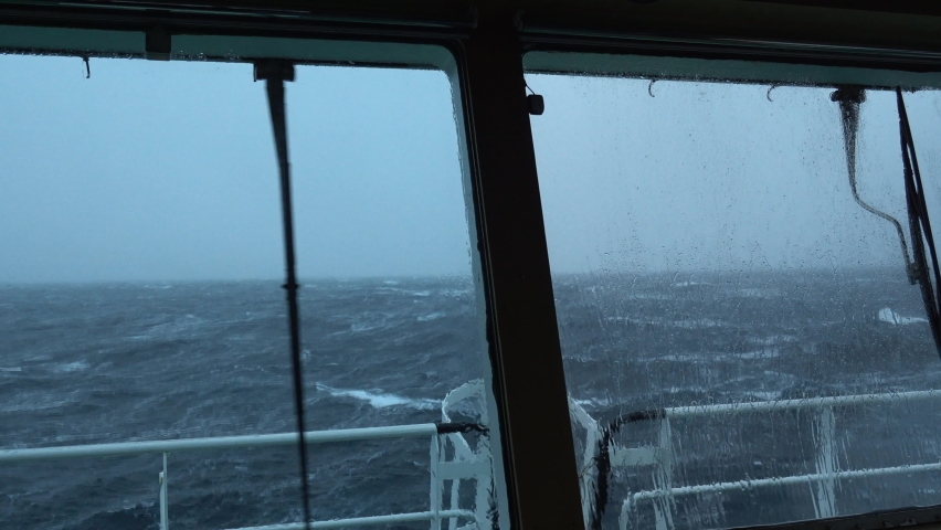 View from ship's bridge. Storm. Ship is rocking. High waves. White foam on the water. Windshield wiper works. Royalty-Free Stock Footage #1071769192
