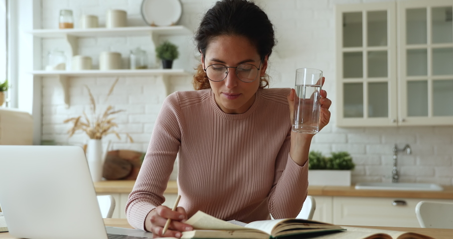 Serious focused woman reading textbook, hold pencil take notes, writes down useful information from printed educational literature, reducing thirst drink still water. Study, gain new knowledge concept Royalty-Free Stock Footage #1071802555