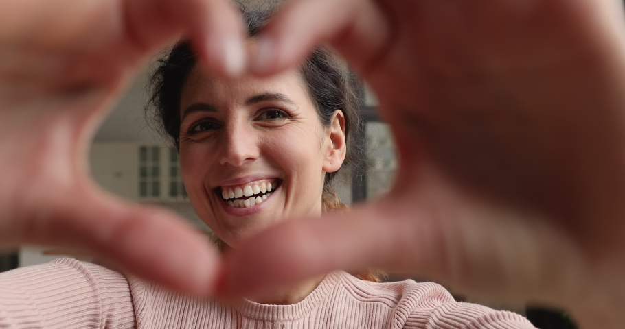 Close up view face of lovely 30s happy smiling female vlogger gives love to followers, woman makes with fingers heart shape, symbol of devotion sign of sincere feelings. Volunteering, charity concept Royalty-Free Stock Footage #1071802915