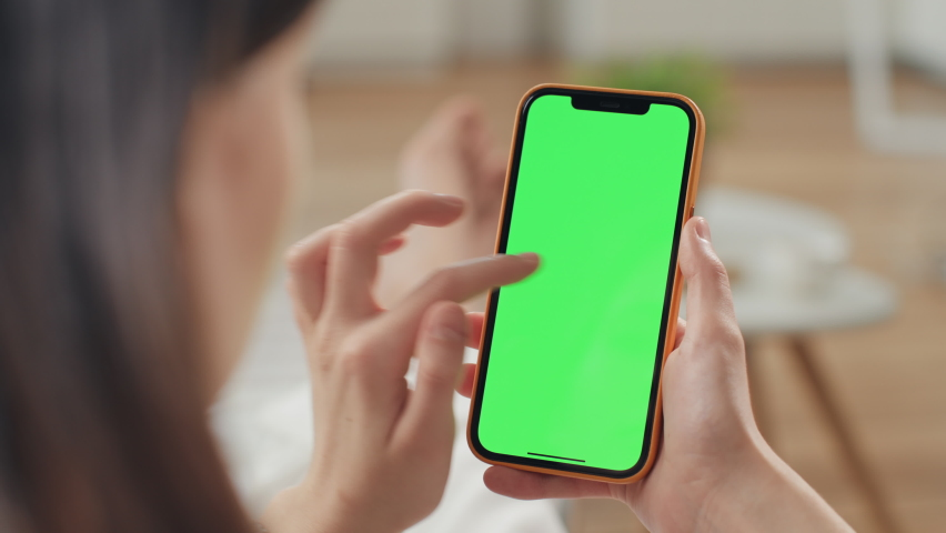 Russia - February 17 2021: Use green screen for copy space closeup. Chroma key mock-up on smartphone in hand. Woman holds mobile phone iPhone and swipes photos or pictures left indoors of cozy home