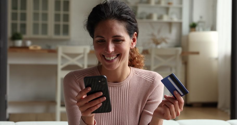 Woman customer hold credit card smartphone buying online use internet retail services. Happy female shopper enjoy instant mobile payments, purchasing in webstore. E-banking app, secure e-pay concept Royalty-Free Stock Footage #1071895321