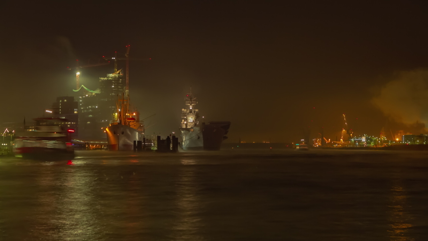 extraordinary long exposure time lapse shot of the port of Hamburg with an aircraft carrier on the bank with spectacular fog and many boats
