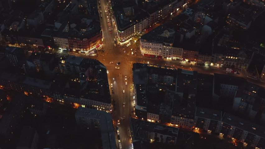 Aerial Birds Eye View over Berlin, Germany Neighborhood, intersection at night with glowing street traffic city lights at Rosenthaler Platz, Top View of Cityscape at Night