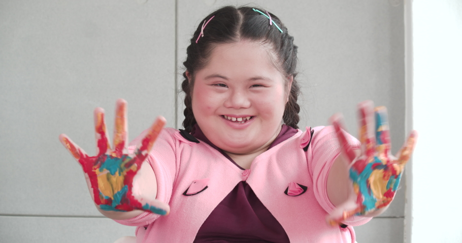 Portrait of asian girl with down syndrome smiling and looking to camera. Little kid show her hands with colorful painted in art class. Education, relationship and humanity concept. Royalty-Free Stock Footage #1071956197