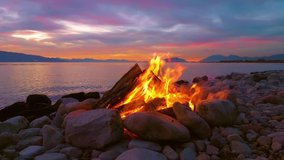A beautiful bonfire. A burning bonfire on the bank of the river. Lake, sea, mountains. Wildlife panorama. Looped video, Looped video. Infinity footage. Cyclic footage. 4K