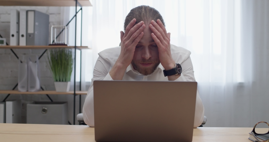 Frustrated Businessman reading on Laptop Bad News having Financial Problems. Young Bearded Man-manager Worried about Problem while Looking at Notebook Screen. Sitting at Home Office. Bankruptcy.