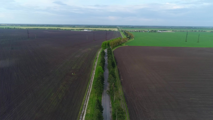 Country road, fields and arable land. Beautiful rural landscape, aerial view. Highway on the background of agricultural land | Shutterstock HD Video #1072034209