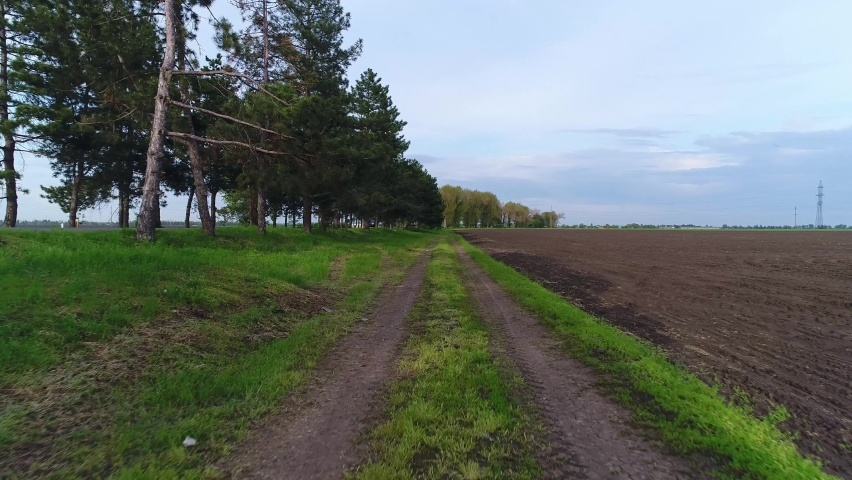 Rural dirt road, track from tractor wheels. Country highway, arable agricultural field | Shutterstock HD Video #1072034215