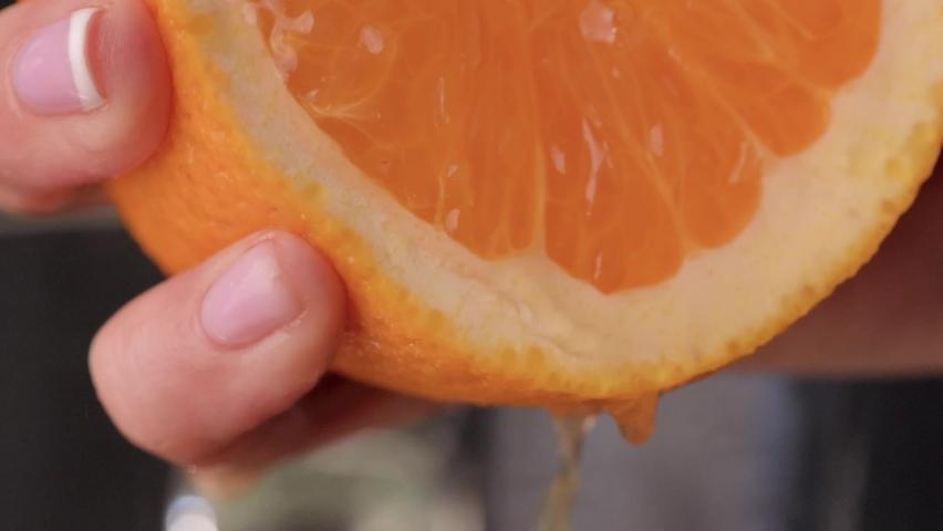 Squeeze orange juice. sliced orange fruit with drops of juice falling from it in slow motion. Close Up macro shot. Fresh fruit
