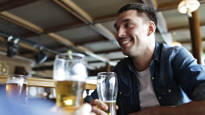 People, leisure and communication concept - happy young man drinking beer with friends at bar or pub | Shutterstock HD Video #10720700