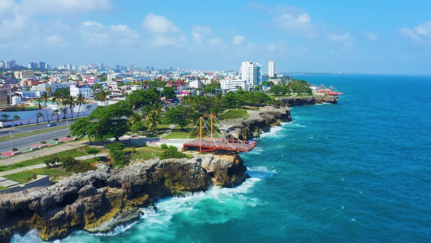 Beautiful cityscape on the shores of the blue Caribbean Sea. A city on the rocky coast of the Atlantic Ocean. City and sea 4k background. Santo Domingo Dominican Republic.