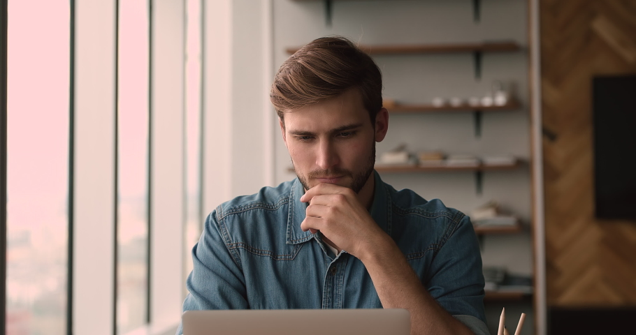 Serious concentrated millennial office manager sit at workplace in modern office working on laptop, solve business remotely texting e-mail, do telecommute creative task looking pensive and thoughtful Royalty-Free Stock Footage #1072143596