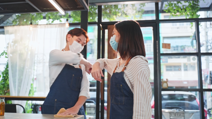 Asian cafe business owner wear protective mask due to Covid19, walk in restaurant with confidence and greeting waiter by elbow bump. Attractive beautiful girl feel happy for new normal in coffee shop. Royalty-Free Stock Footage #1072147718