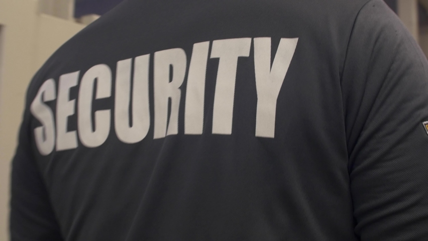 A tracking shot of a security guard in uniform patrolling in a commercial area. Royalty-Free Stock Footage #1072209032