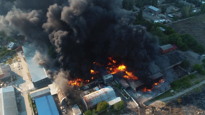 Severe fire in the warehouse. Black smoke in the sky. Drone filming over a large-scale fire. Grain video Royalty-Free Stock Footage #1072229834