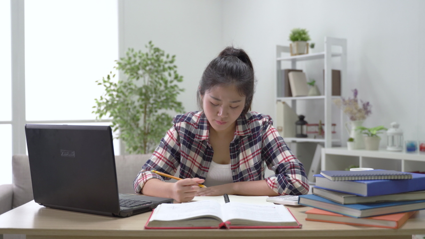 fast forward of female student studying with the distraction of websites and responding friend's message on the laptop while preparing for calculus quiz using a scientific calculator Royalty-Free Stock Footage #1072237604