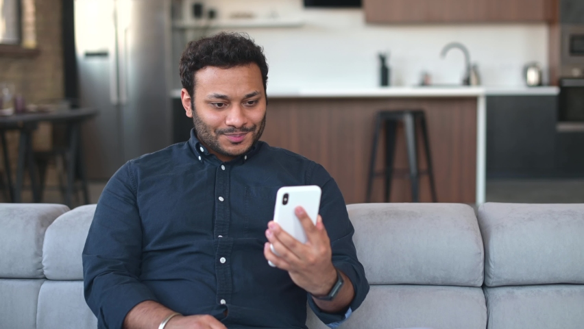Indian guy using mobile app for video connection, holding smartphone and waving to online interlocutor, happy hindu guy enjoying chatting via video call, staying in touch with family on the distance Royalty-Free Stock Footage #1072238078