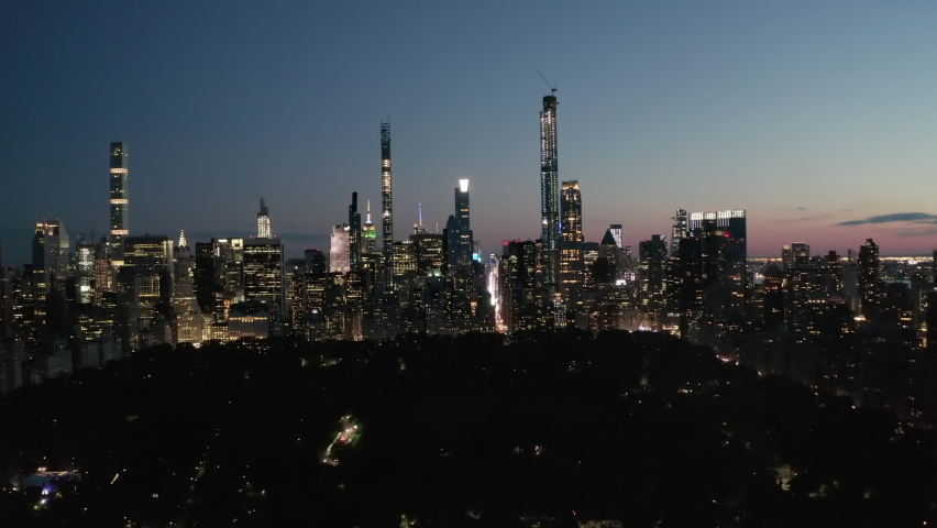 Moving Time Lapse Hyper Lapse over New York City Central Park at Night Towards Skyline of Manhattan Skyscraper with glowing City lights, Aerial Hyperlapse