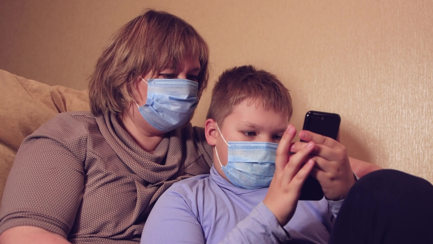 An adult female client and a boy wearing medical masks shop online. Happy female shopper with instant easy mobile payments takes advantage of discounts in e-banking online store. Royalty-Free Stock Footage #1072247198