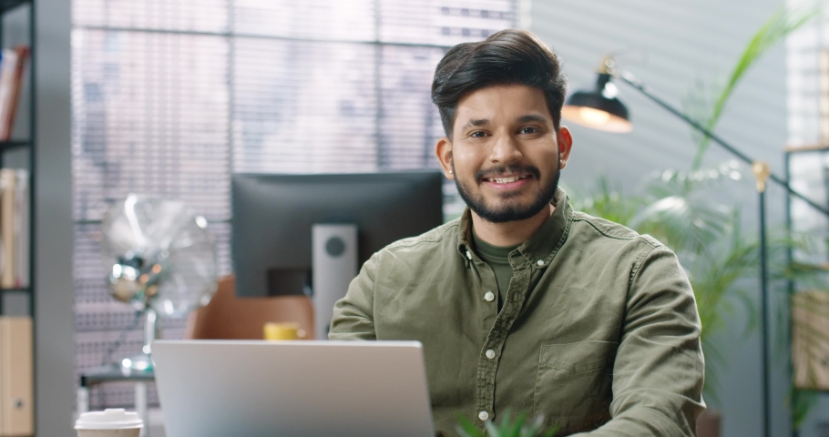 Close up portrait of happy handsome young Hindu male worker sitting at desk in modern cabinet and tapping on laptop browsing online at office removing medical mask looking at camera with smile on face Royalty-Free Stock Footage #1072262255
