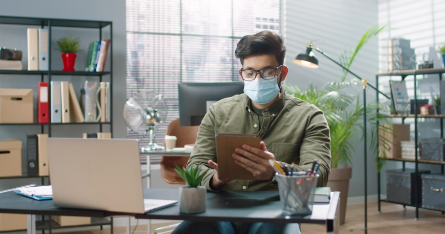 Close up portrait of handsome young concentrated Hindu businessman in medical mask sitting at desk and typing on tablet device searching internet at office in cabinet. Corporate work, job concept Royalty-Free Stock Footage #1072262273