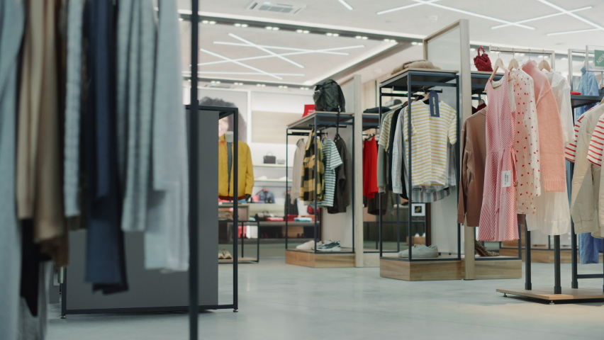 Shopping Clothing Store Interior. Modern Fashionable Shop, Clothes for Every Taste. Stylish Brand Design, Fashionable Colors, Quality Sustainable Materials. No People. Low Dolly Establishing Shot Royalty-Free Stock Footage #1072294157