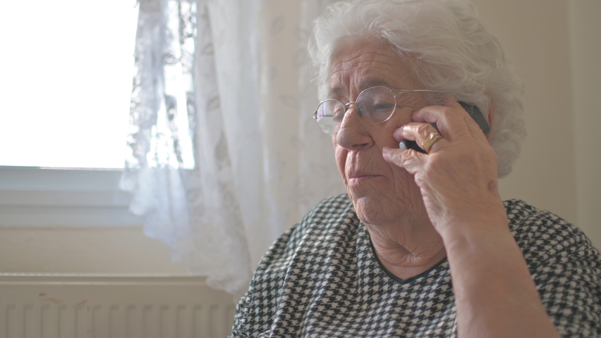 Senior woman talking on mobile phone at home.