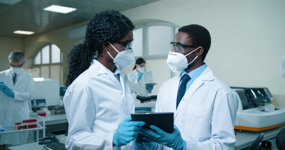 Portrait of African American young male and female medical experts in masks and white coats standing in clinic laboratory and tapping on tablet discussing analysis results. Healthcare, lab concept Royalty-Free Stock Footage #1072400933