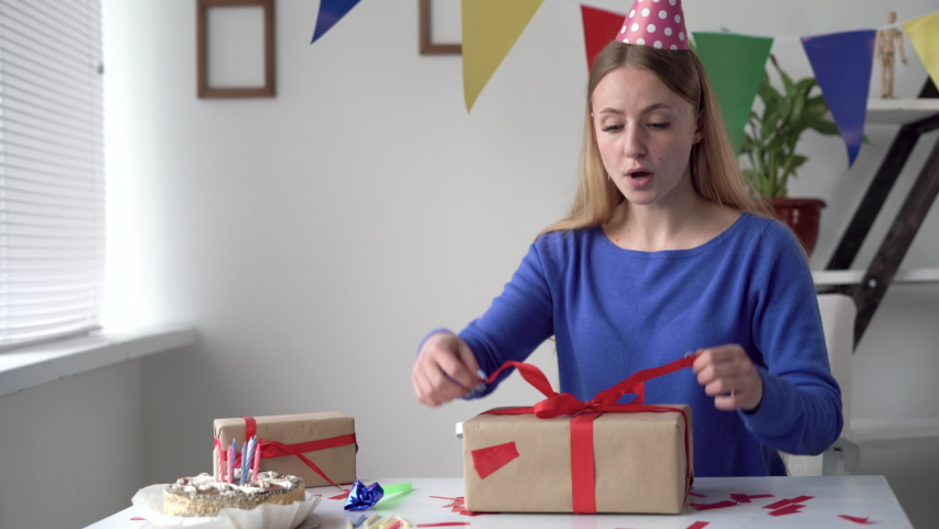 Birthday at home alone. A young woman sits at a table unties a bow on a large craft box. Cheerful and happy birthday lady. Royalty-Free Stock Footage #1072449614