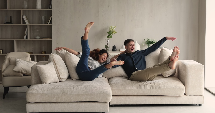 Happy Hispanic couple jumping on soft sofa laugh enjoy relax, rest on cozy couch feel overjoyed celebrate move day to own home, rented flat. Homeowners family, fashionable furniture store ad concept Royalty-Free Stock Footage #1072486949