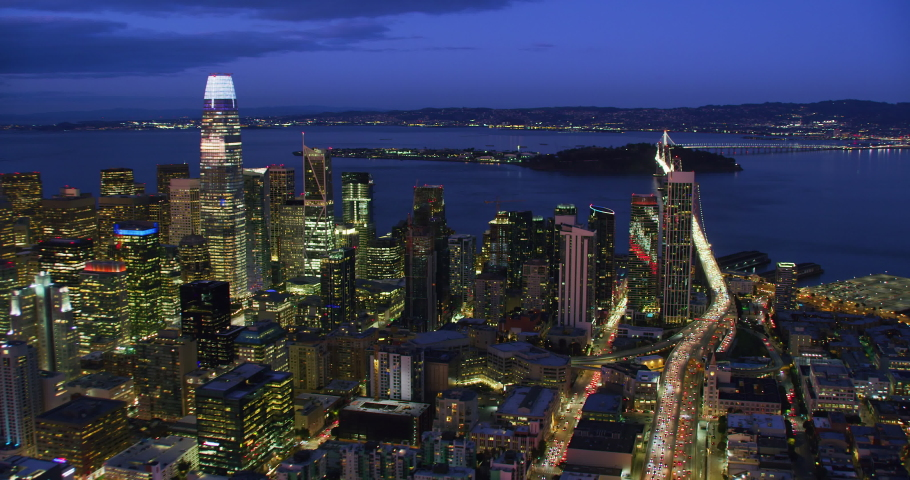 San Francisco Financial District aerial view. Famous skyscrapers at dusk. Bay bridge in the background. California, United States. Shot in 8K.