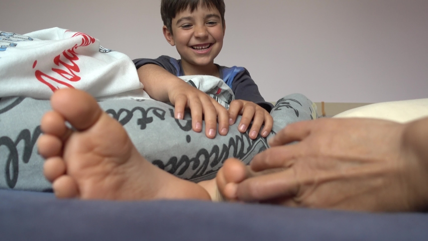 4K Cute child in bed ticklish when hand tickles his soles