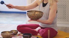 Woman playing on Tibetan singing bowl while sitting on yoga mat. Vintage tonned. stock footage. Slow Motion video. Close up