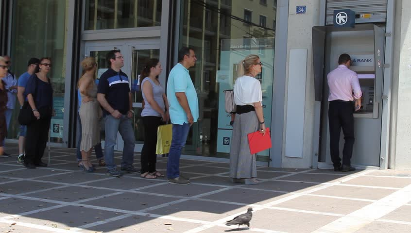 ATHENS, GREECE - JULY 7TH, 2015: Citizens line up to use an ATM outside the Alpha Bank, on July 7th, 2015, in Athens, Greece. A withdraw limit of 60 euros per day allowed by the capital controls.