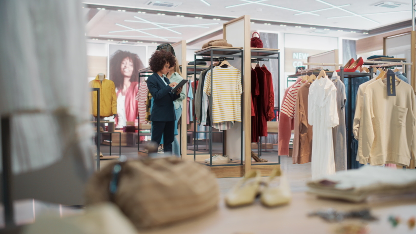 Customers Shopping in Modern Clothing Store, Retail Sales Associate Assists Client. Diverse People in Fashionable Shop, Choosing Stylish Clothes, Colorful Brand Designs, Quality Sustainable Materials.