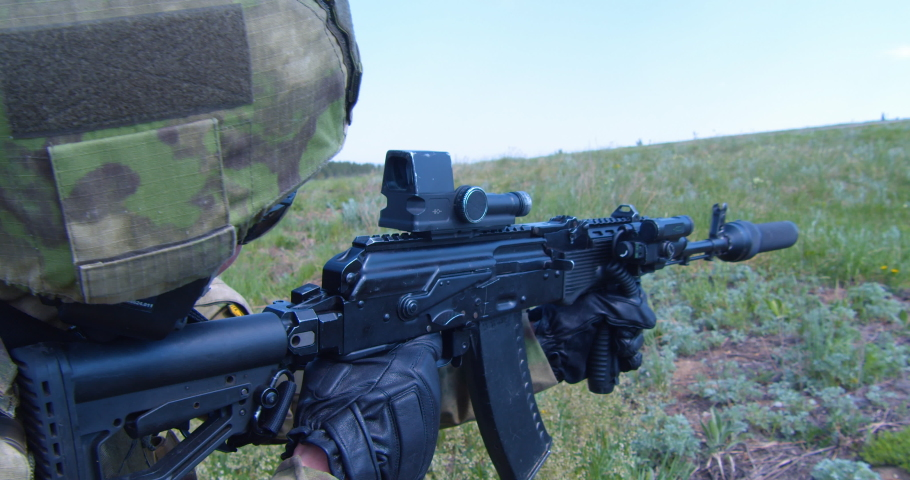 Russian army soldier holds a machine gun forward to attack the enemy on the battlefield.