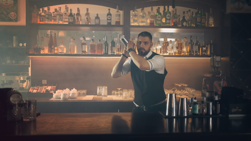 The profession of bartender. The process of making a cocktail at a bar in a restaurant. the bartender mixes the ingredients of an alcoholic cocktail by shaking a shaker.   Shutterstock HD Video #1072826510