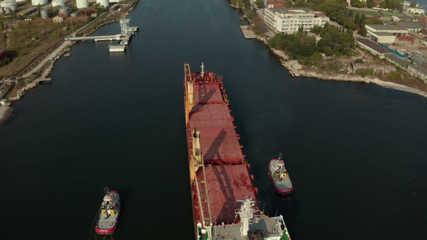 Aerial view of cargo ship calling into the port for repair under the guide of tugboats.