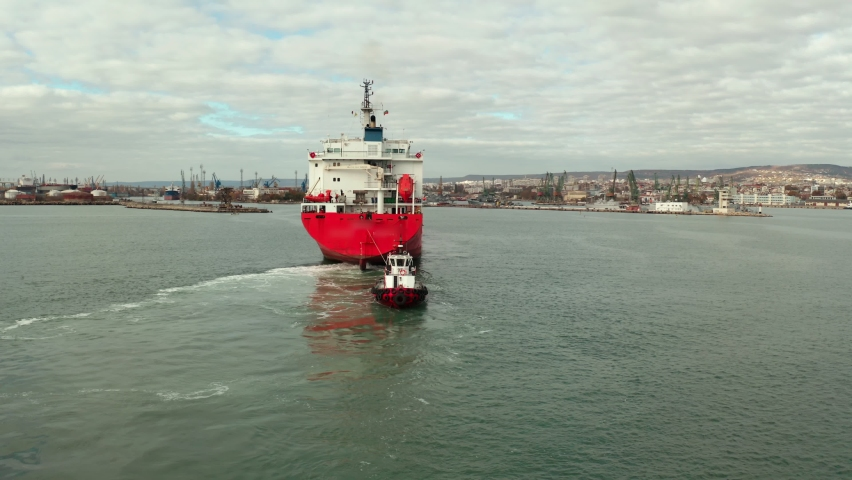 Aerial view of massive cargo ship calling into the port for repair under the guide of tugboats.
